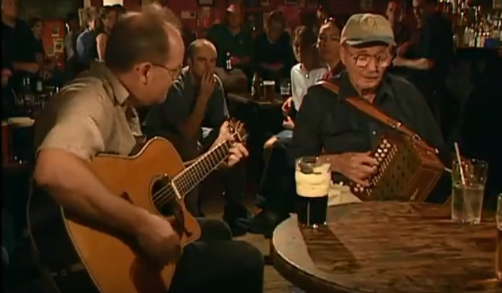 A Man playing an accordion with a guitar player in a pub in Ireland