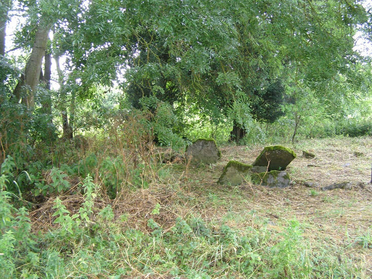 A Country churchyard showing head stones falling over with over grown grass and trees